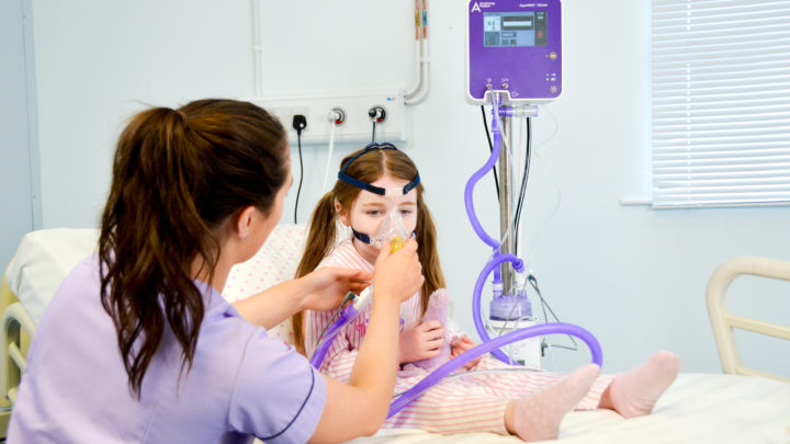Photo of staff and child with paediatric face mask